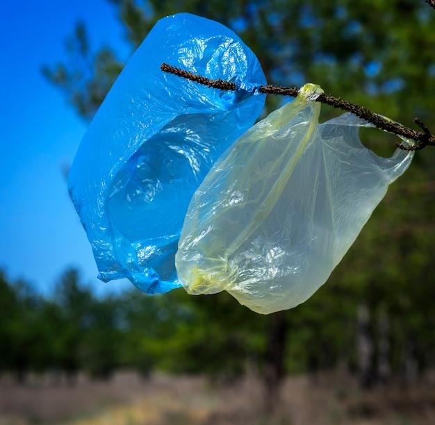 Twee gebruikte lege plastic zakken die op een tak hangen