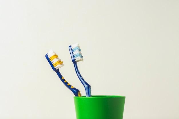 Twee gebruikte tandenborstels in een plastic beker op een witte achtergrond. het concept van het wisselen van tandenborstels, mondhygiëne, tandheelkunde, vriendelijke familie.