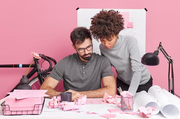 Twee geconcentreerde ontwerpers praten over informatie om nieuwe schetsen te maken, voorbereiden architectuurproject bezig met papierwerk poseren op desktop met blauwdrukken hebben serieuze uitdrukkingen. samenwerking