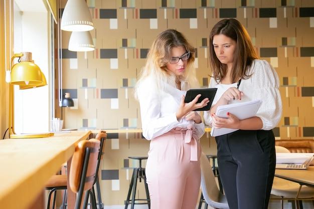 Twee geconcentreerde vrouwen die op tabletscherm kijken