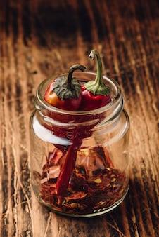 Twee gedroogde rode chilipepers in pot met gemalen pepers