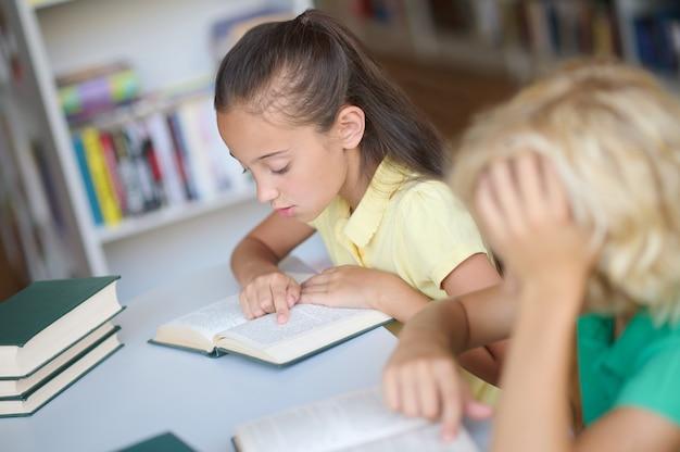 Twee gefocuste schoolkinderen die samen studeren in de bibliotheek