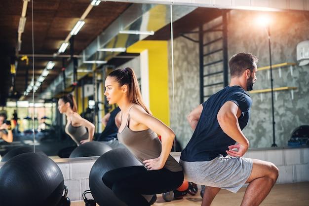 Twee gefocuste sterke gympartners doen squats leunend op elkaars rug.