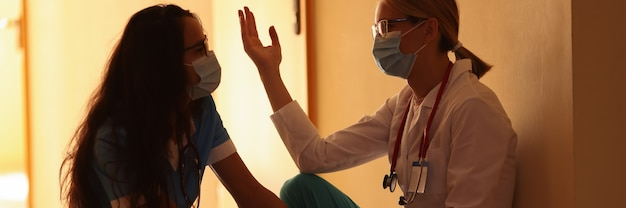 Twee gefrustreerde artsen zitten in de ziekenhuisgang