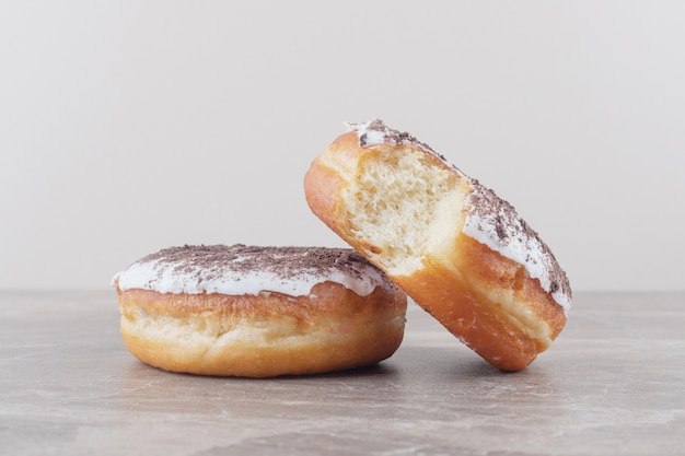 Twee geglazuurde donuts op marmer