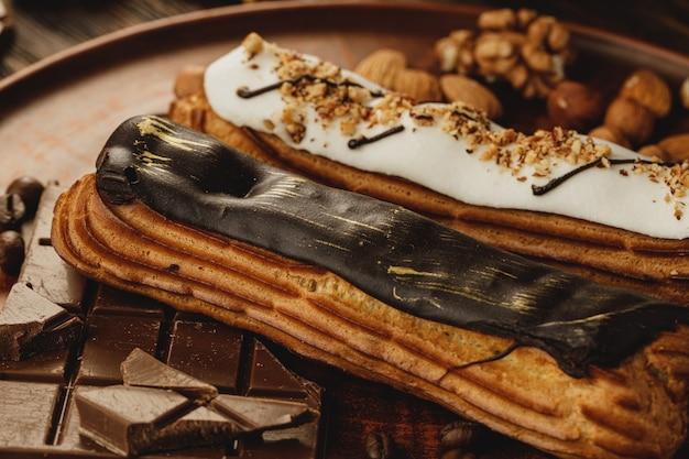 Twee geglazuurde eclairs versierd met noten en koffie
