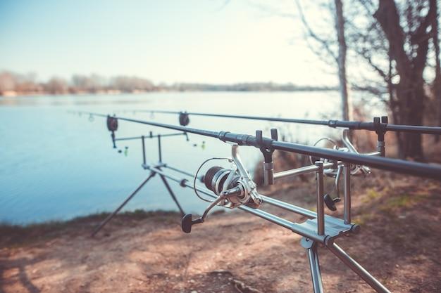 Twee gegoten hengels op het rek bij het meer, klaar om te vissen, karpervissen, vissen, sportconcept