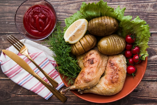 Twee gegrilde kippenpoten met fruit en groenten in kom