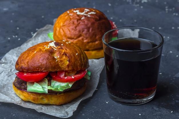 Twee gegrilde rundvleesburgers met sla en tomaat en een glas frisdrank