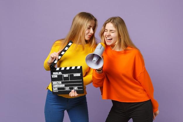 Twee gekke jonge blonde tweelingzusters meisjes houden klassieke zwarte film filmklapper, schreeuwen op megafoon geïsoleerd op violet blauwe muur. mensen familie levensstijl concept. .