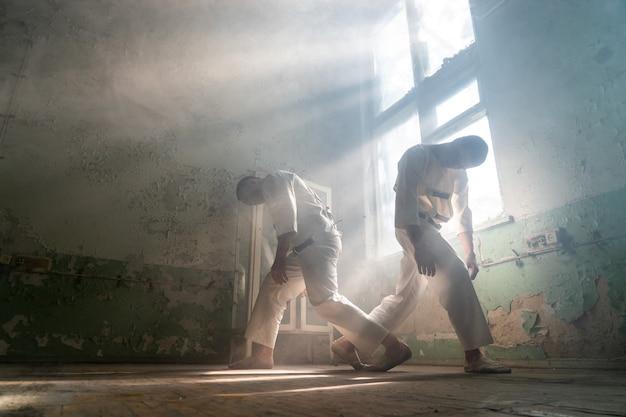 Twee gekke mannen in dwangbuizen zitten in een verlaten kliniek.