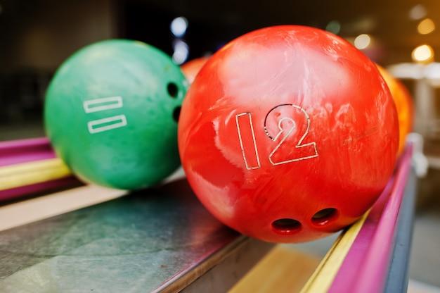 Twee gekleurde bowlingballen van nummer 12 en 11