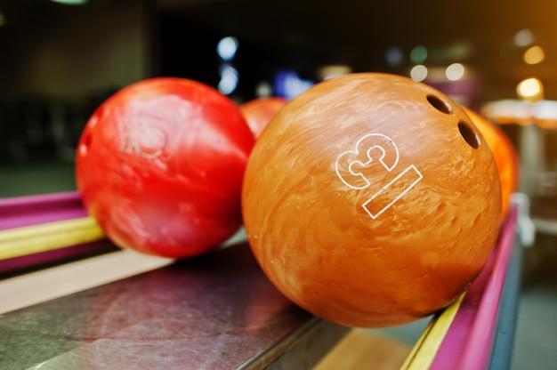 Twee gekleurde bowlingballen van nummer 13 en 12