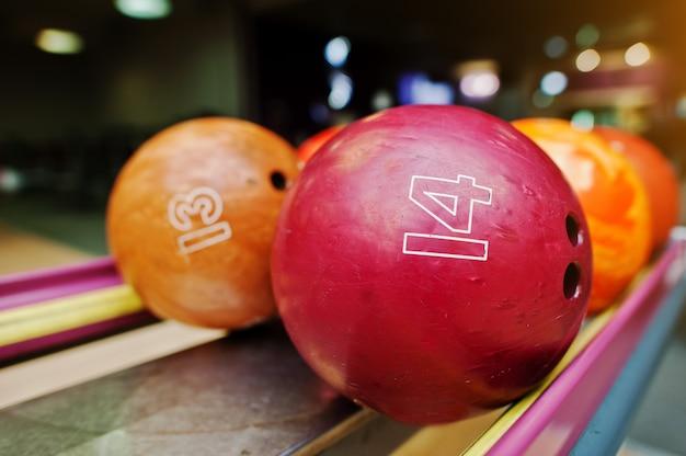 Twee gekleurde bowlingballen van nummer 14 en 13