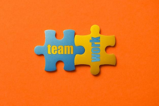 Twee gekleurde details van puzzel met tekst teamwerk aan oranje, geel en blauw,