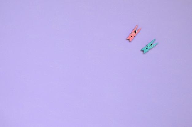 Twee gekleurde houten pinnen liggen op textuurachtergrond van violet de kleurendocument van de manierpastelkleur