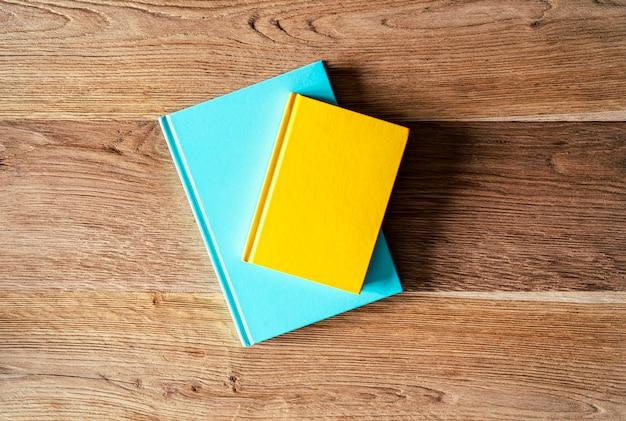 Twee gekleurde notitieboekjes blauw mintgroen en geel op een houten tafel