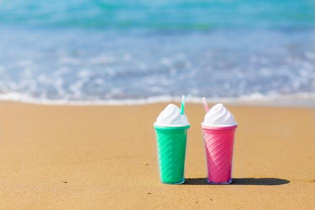 Twee gekleurde plastic cocktailglazen op de zandmuur van het overzees. zomervakantie concept