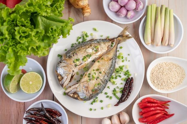 Twee gekookte makreel, geplaatst in een witte schotel, bestrooid met lente-uitjes.