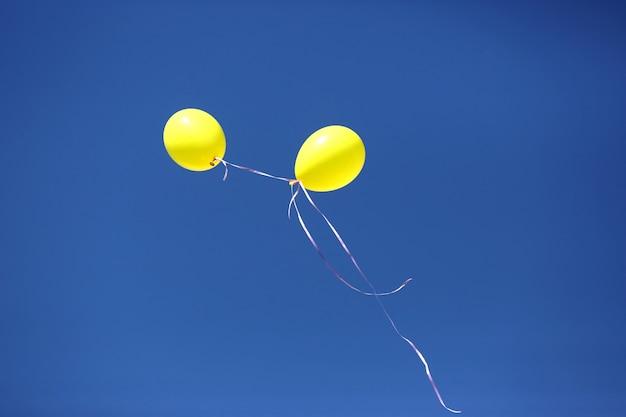 Twee gele ballon tegen een blauwe hemel