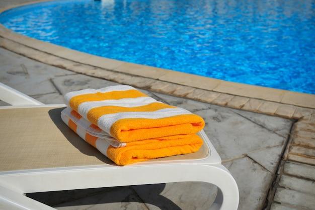 Twee gele gestreepte handdoeken liggen op een ligbed bij een zwembad