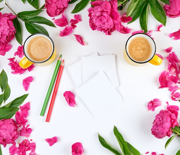 Twee gele kopjes koffie op een witte achtergrond, langs de omtrek van bloeiende rode pioenrozen