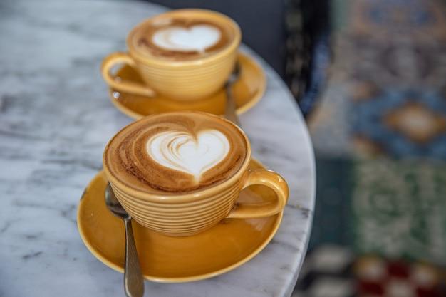 Twee gele kopjes warme cappuccino op marmeren tafelondergrond. hartvorm als kunst latte voor liefde
