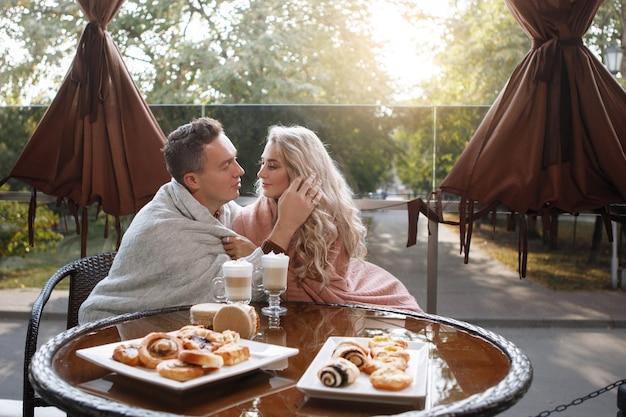 Twee geliefden, een man en een vrouw aan een tafel in een café. knuffel, streel, drink latte. gelukkig traditioneel paar, gezinsgeluk.