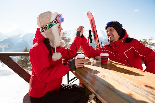 Twee geliefden en vrienden genieten van een drankje in de bar in het skiresort.