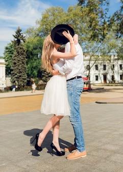 Twee geliefden, geweldig paar in witte lente-outfit knuffelen op straat