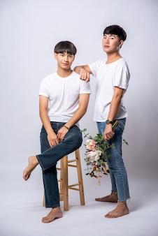 Twee geliefden, handen die op hun schouders rusten en op een stoel zitten.