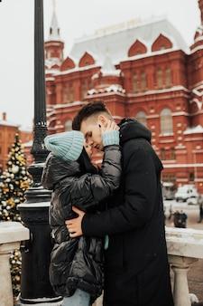 Twee geliefden knuffelen en kussen op straat in de stad