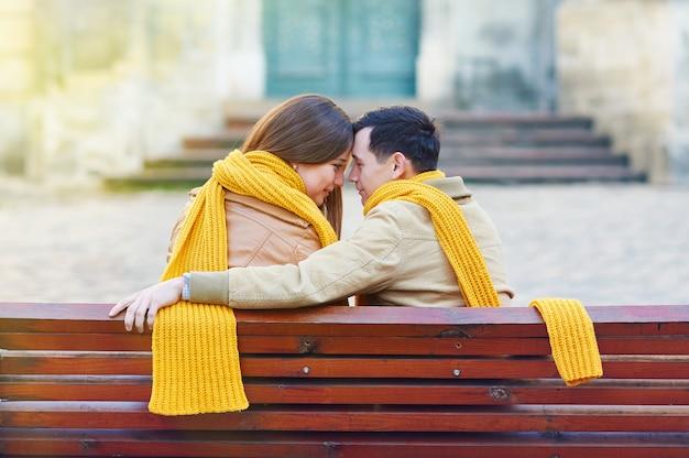 Twee geliefden zittend op een bankje in het park en houden zichzelf door handen