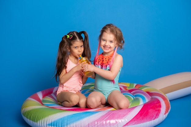 Twee gelukkig kind meisje in zwempak drinken sinaasappelsap zittend op kleurrijke opblaasbare matras.