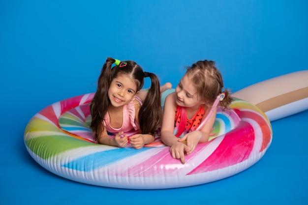 Twee gelukkig kindmeisje in zwempak dat op kleurrijke opblaasbare matraslolly ligt.