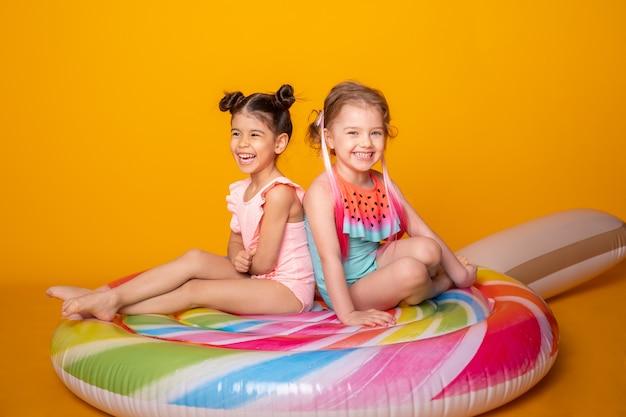 Twee gelukkig klein meisje in zwemkleding zittend op kleurrijke opblaasbare matras lolly.