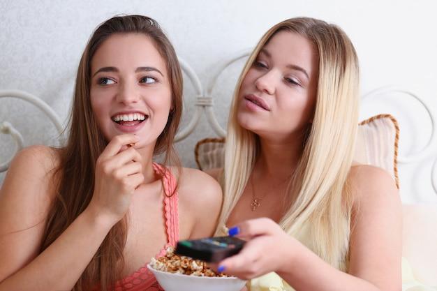 Twee gelukkig lachend vriendinnen eten popcorn in bed