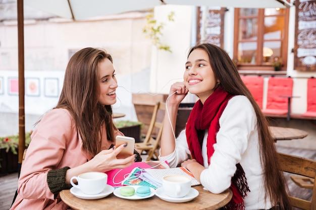 Twee gelukkige aantrekkelijke jonge vrouwen luisteren naar muziek van smartphone met koptelefoon in openluchtcafé
