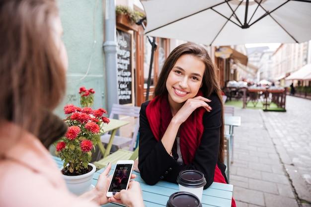 Twee gelukkige aantrekkelijke jonge vrouwen praten en het gebruik van mobiele telefoon op terras
