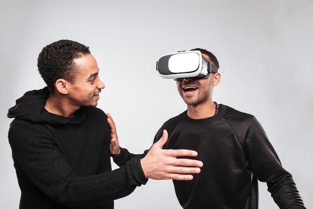 Twee gelukkige afrikaanse jonge mannen met behulp van 3d-virtual reality-apparaat.