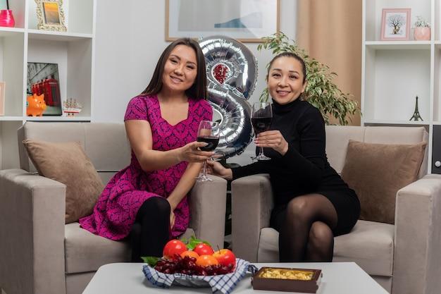 Twee gelukkige aziatische jonge vrouwen in mooie jurken zittend op een stoel met nummer acht vormige ballon glimlachend vrolijk drinken wijn vieren internationale vrouwendag in lichte woonkamer
