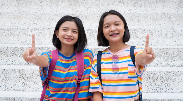 Twee gelukkige aziatische meisjes tonen één vinger met gelukkige emotie.