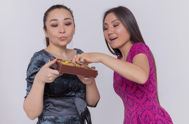 Twee gelukkige aziatische vrouwen die doos met chocoladesuikergoed houden die de dag van internationale vrouwen vieren die vrolijk glimlachend over witte muur staan