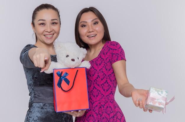 Twee gelukkige aziatische vrouwen die papieren zak met teddybeer houden