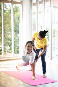 Twee gelukkige aziatische vrouwen in yoga houdingen in yogastudio met natura llight setting scene / oefeningsconcept / yoga praktijk / kopieer ruimte / yogastudio