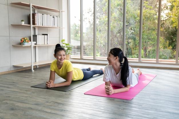 Twee gelukkige aziatische vrouwen in yoga houdingen in yogastudio met natuurlijk licht plaatsend scène / oefeningsconcept / yogapraktijk / exemplaarruimte / yogastudio