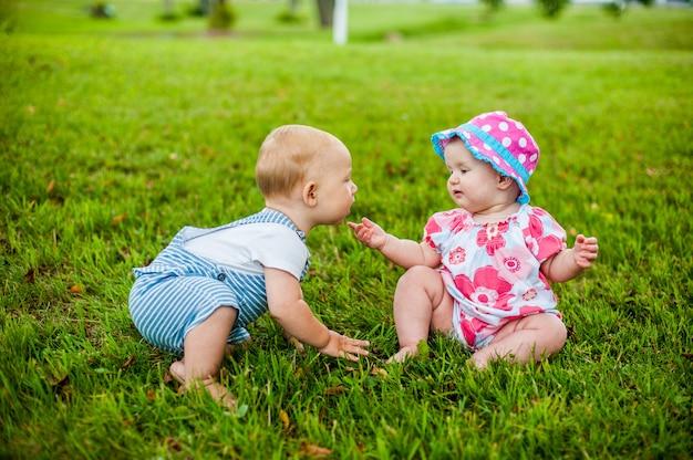 Twee gelukkige babyjongen en een meisje van 9 maanden oud, zittend op het gras en interactie, praten, kijken naar elkaar.