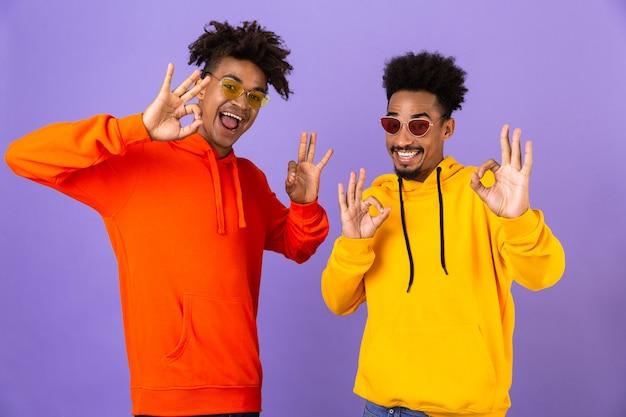 Twee gelukkige beste vrienden gekleed in kleurrijke hoodies
