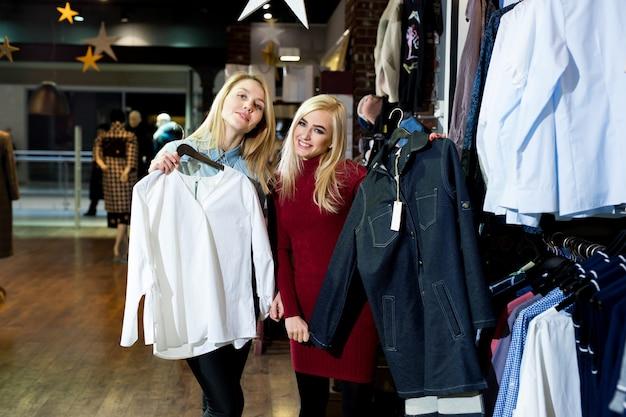 Twee gelukkige beste vriendinnen kijken naar de kwaliteit van een shirt dat op een rail in de kledingwinkel hangt