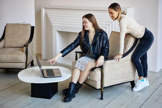 Twee gelukkige blanke vrouwen werken met laptop op kantoor